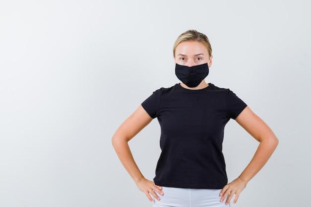 Mulher loira segurando as mãos na cintura em camiseta preta, calça branca