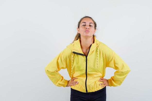 Mulher loira segurando as mãos na cintura enquanto manda beijos para a frente com uma jaqueta amarela e calça preta e parece feliz