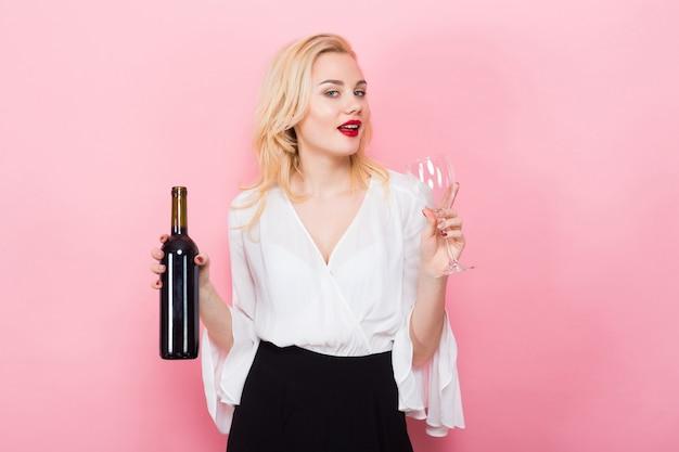 Mulher loira segurando copo e garrafa de vinho