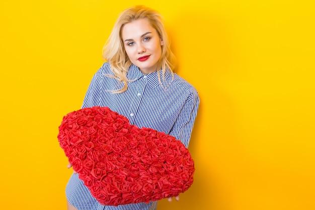 Mulher loira segurando coração grande flor vermelha.