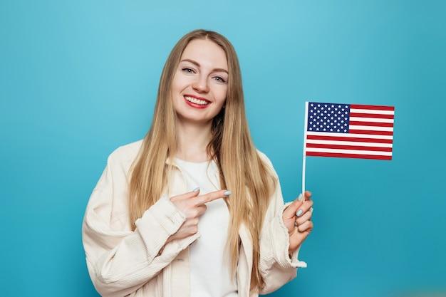 Mulher loira segurando e apontando o dedo para uma pequena bandeira americana