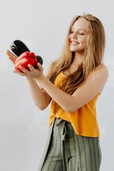 Mulher loira segurando frutas e vegetais