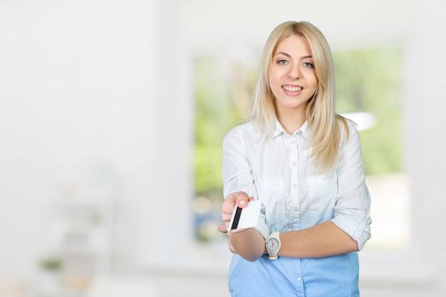 Mulher loira segurando o cartão de crédito