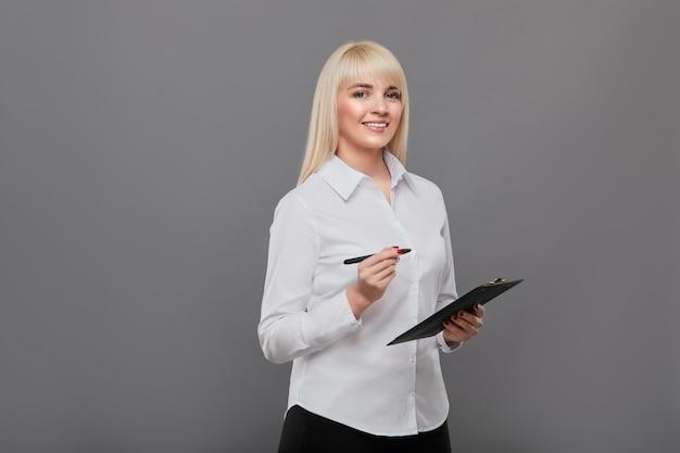Mulher loira segurando o tablet fazendo questionário.
