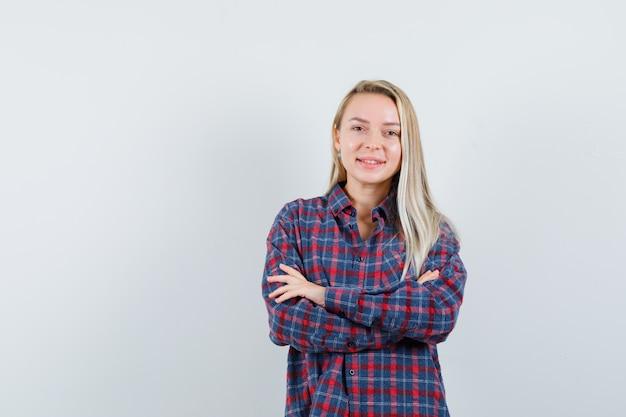 Mulher loira segurando os braços cruzados e sorrindo graciosamente em camisa xadrez e olhando atraente, vista frontal
