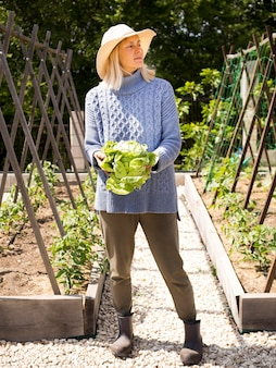 Mulher loira segurando repolho verde fresco nas mãos
