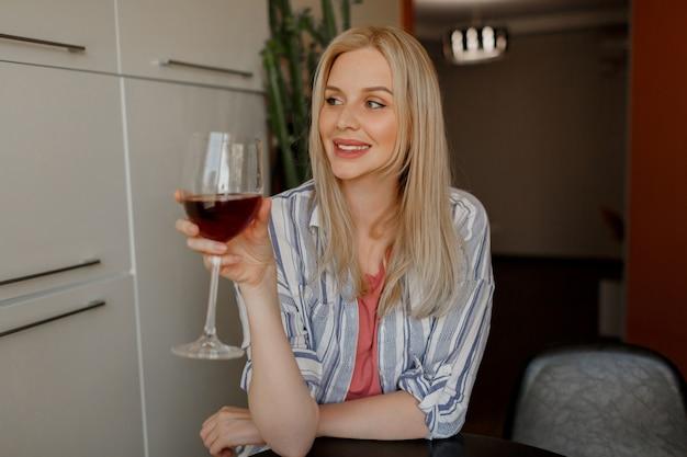 Mulher loira segurando um copo de vinho tinto na cozinha dela.