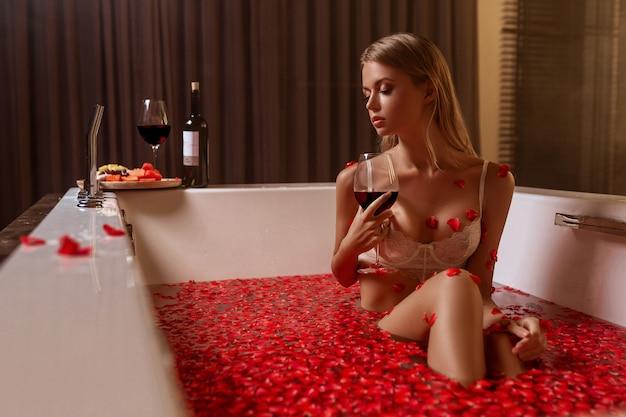 Mulher loira segurando um copo de vinho tinto no banho com pétalas de rosa