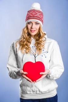 Mulher loira segurando um coração vermelho. dia dos namorados