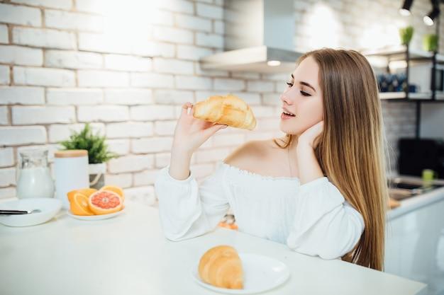 Mulher loira segurando um croissant e sorrindo comida saudável enquanto está sentado na cadeira.