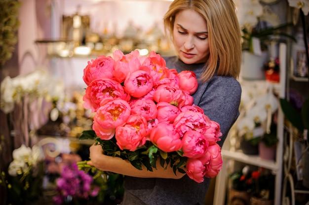 Mulher loira segurando um grande buquê de peônias rosa