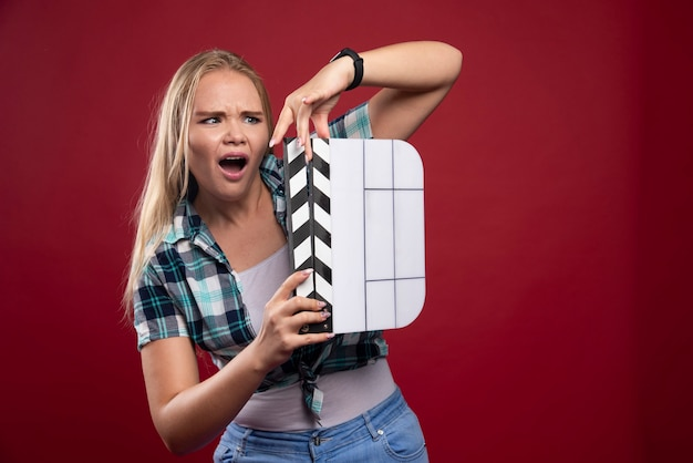 Mulher loira segurando uma claquete de produção de filme e parece confusa e cansada.