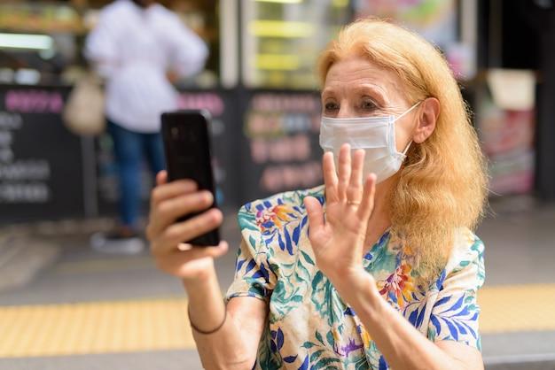 Mulher loira sênior com máscara fazendo videochamada em uma cafeteria ao ar livre