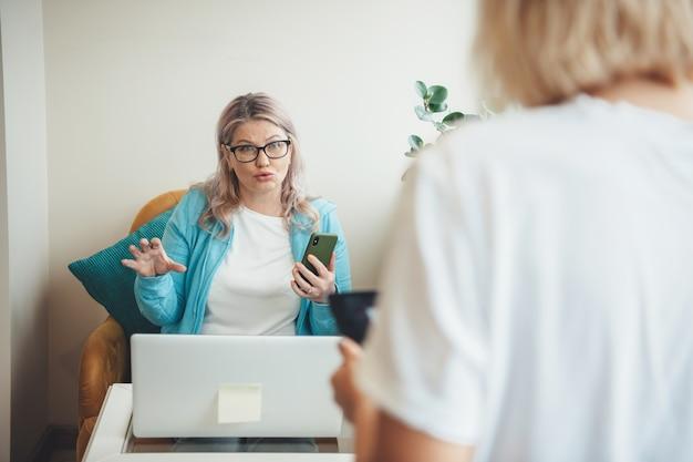 Mulher loira sênior com óculos, segurando um telefone, explicando algo para um cliente usando um laptop e trabalhando em casa