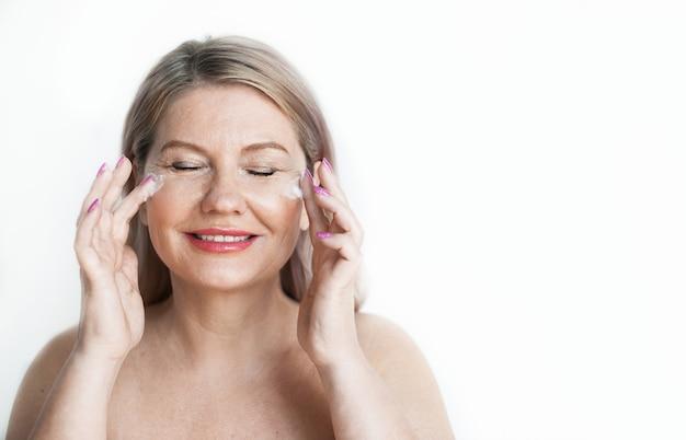 Mulher loira sênior com ombros nus, aplicando um creme no rosto e sorrindo em uma parede branca com espaço livre