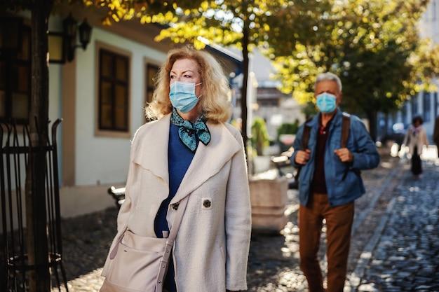 Mulher loira sênior com uma máscara protetora em andar no centro da cidade em um dia ensolarado de outono.