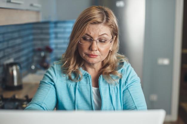 Mulher loira sênior está concentrada trabalhando em casa no laptop remotamente usando óculos na cozinha