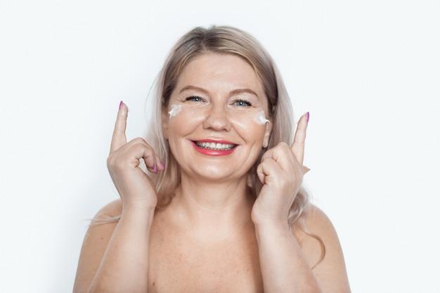 Mulher loira sênior está sorrindo para a câmera com os ombros nus, aplicando um creme anti-envelhecimento nas bochechas
