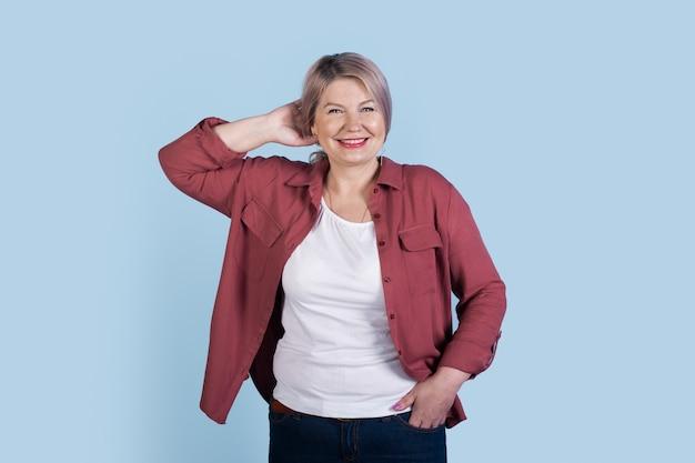 Mulher loira sênior está sorrindo para a câmera, vestindo uma camisa e posando em uma parede azul do estúdio