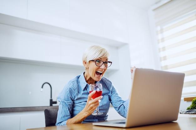 Mulher loira sênior, sentado à mesa de jantar, bebendo vinho, olhando para o laptop e torcendo pela conquista