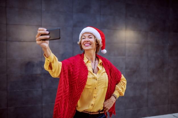 Mulher loira sênior sorridente atraente com chapéu de papai noel na cabeça, posando e tomando selfie em frente a parede ao ar livre.