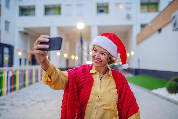 Mulher loira sênior sorridente atraente com chapéu de papai noel na cabeça, posando e tomando selfie em pé ao ar livre.