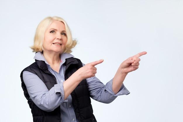 Mulher loira sênior sorrindo apontando os dedos de lado