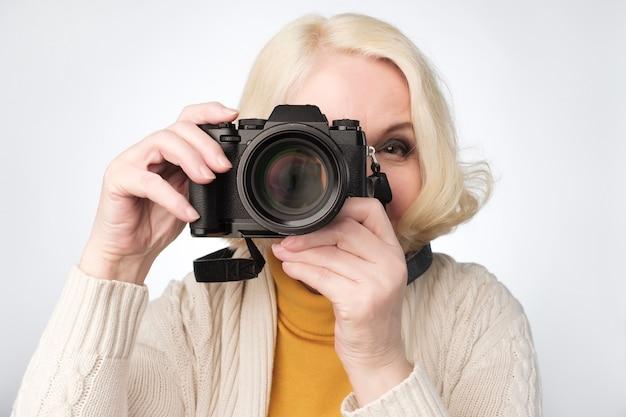 Mulher loira sênior tirando foto com a câmera