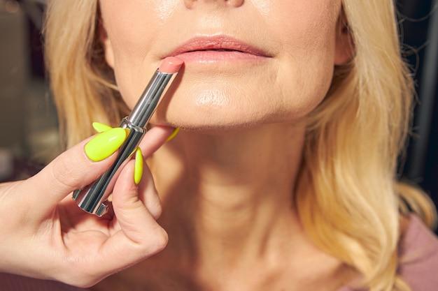 Mulher loira sênior visitando salão de beleza e fazendo maquiagem profissional