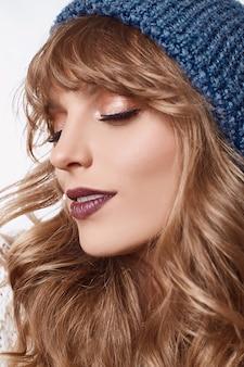Mulher loira sensual com chapéu azul, isolado no fundo branco