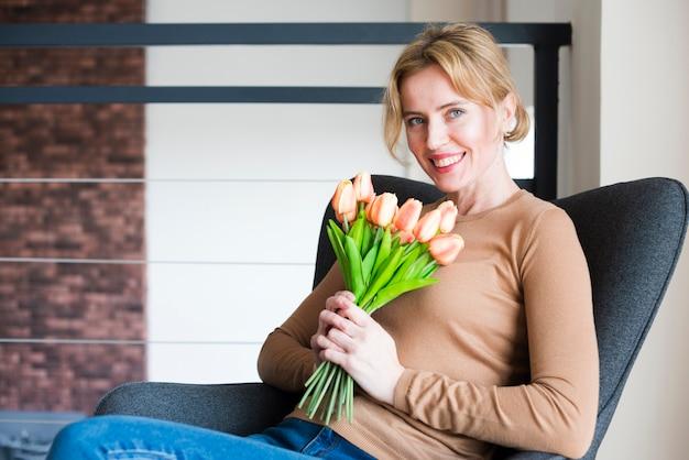 Mulher loira sentada com buquê de tulipas na poltrona