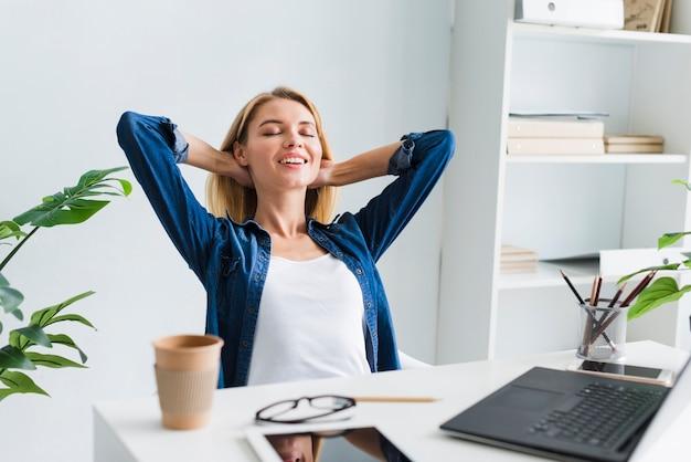 Mulher loira sentada e sorrindo com os olhos fechados no local de trabalho