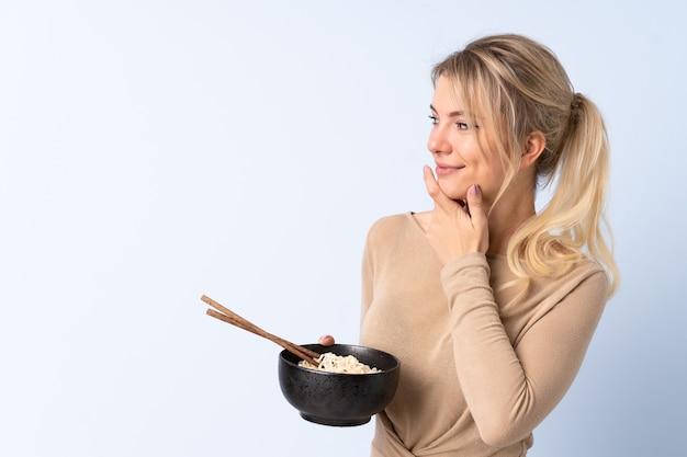 Mulher loira sentada em uma parede azul isolada, pensando em uma ideia e olhando para o lado enquanto segura uma tigela de macarrão com pauzinhos