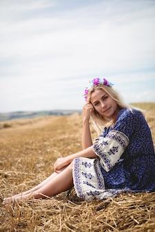Mulher loira sentada no campo
