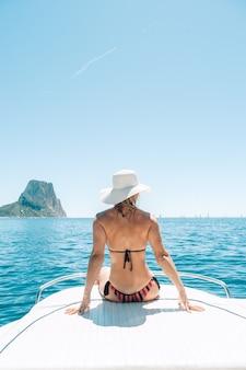 Mulher loira sentada no convés de um barco no mar mediterrâneo