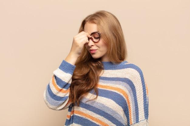 Mulher loira sentindo-se estressada, infeliz e frustrada, tocando a testa e sofrendo de enxaqueca ou forte dor de cabeça