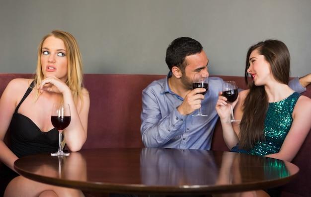 Mulher loira sentindo-se solitária quando duas pessoas estão a flertar ao lado dela