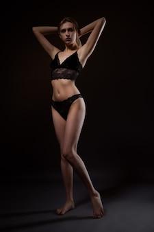 Mulher loira sexy com uma figura linda em roupa íntima de renda preta