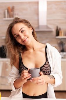 Mulher loira sexy em lingerie tomando café durante o café da manhã, aproveitando a manhã. jovem mulher atraente com tatuagens em lingerie sedutora, segurando uma xícara de chá relaxante na cozinha sorrindo.