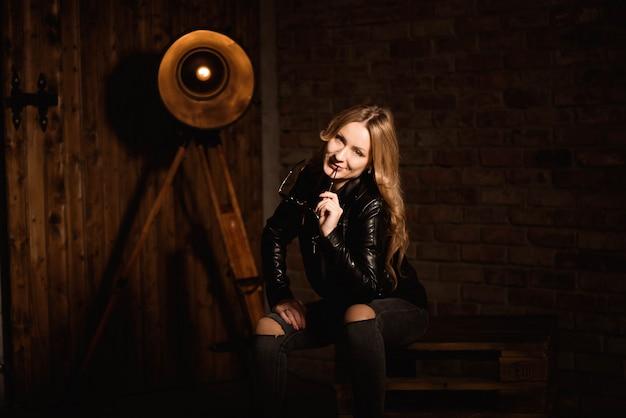 Mulher loira sexy em roupas de couro posando contra a parede de madeira do estúdio.