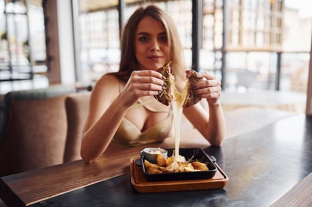 Mulher loira sexy em roupas quentes se senta à mesa e come fast food dentro de casa no café.