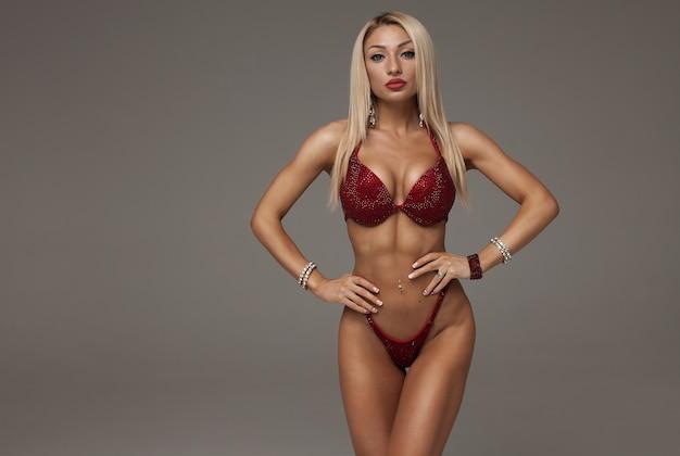 Mulher loira sexy fisiculturista de biquíni em fundo cinza