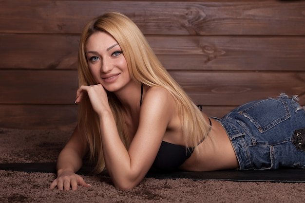 Mulher loira sexy vestindo shorts jeans e mentir
