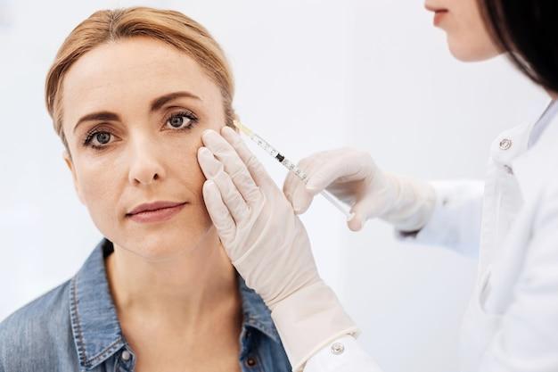 Mulher loira simpática e simpática inclinando levemente a cabeça e tomando uma injeção de botox enquanto visitava um cosmetologista