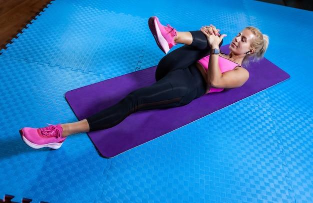 Mulher loira slim fit na esteira fazendo exercícios de aquecimento. mulher apta deita-se no tapete de ioga e pratica o alongamento das pernas e de todo o corpo. estilo de vida saudável, conceito de fitness