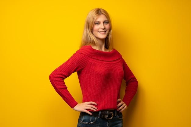 Mulher loira sobre parede amarela posando com os braços no quadril e sorrindo