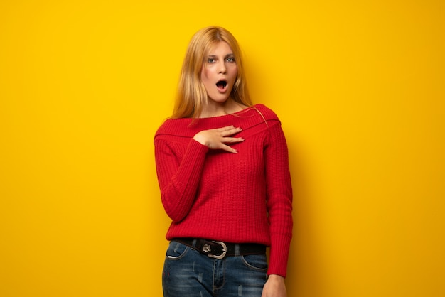 Mulher loira sobre parede amarela surpreso e chocado ao olhar para a direita