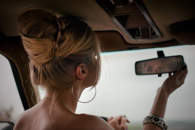 Mulher loira sonhadora se olhando no espelho do carro