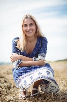 Mulher loira sorridente, agachando-se no campo
