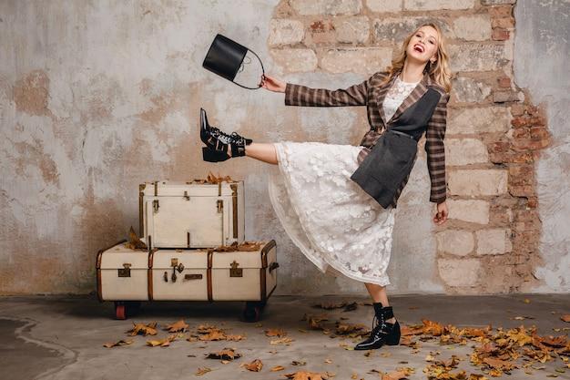 Mulher loira sorridente atraente e elegante com jaqueta quadriculada caminhando contra a parede na rua